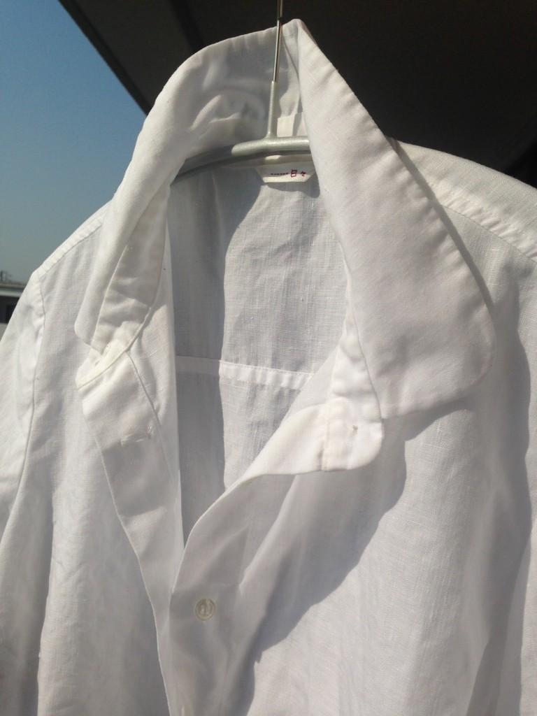 写真:後ろ襟を立て、第2ボタンまで開けた状態で干しているシャツ