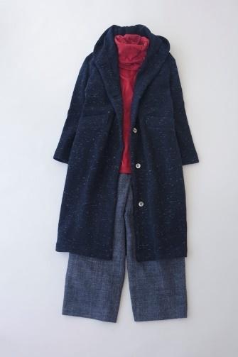 写真:赤のタートルネックにダークブルーのワイドパンツ。ネイビーのフード付きロングコートを羽織って。