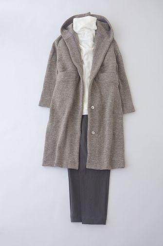 写真:白のタートルネックにダークグレーのテーパードパンツ。ベージュのフード付きロングコートを羽織って。