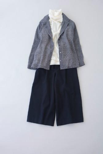写真:白のタートルネックにネイビーのキュロットパンツ。ブルーのジャケットを羽織って。