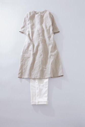 写真:生成りの五分袖ワンピースに白の細身パンツ。