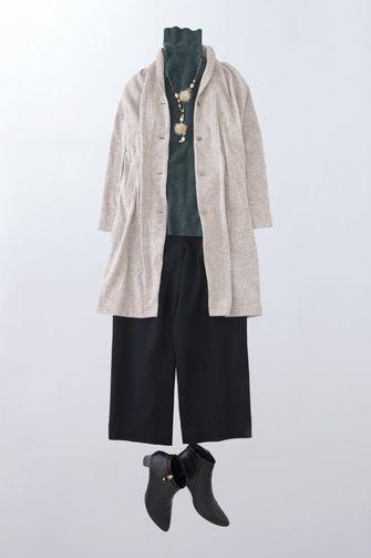写真:深緑色のタートルネックに黒のガウチョパンツ。ベージュのロングカーディガンを羽織って。