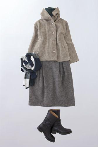 写真:ベージュのフード付きショートコートにツイードのスカート、黒のブーツ。