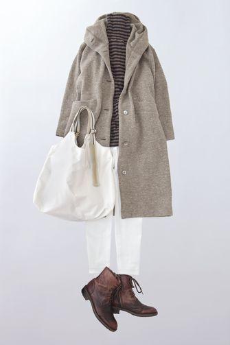 写真:茶色のボーダータートルネックに白のパンツ、ベージュのフード付きロングコートを羽織って。