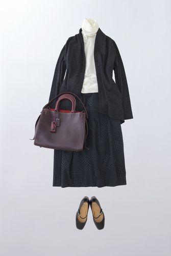 写真:白のタートルネックに黒のカーディガンジャケット、黒のキュロットパンツ。