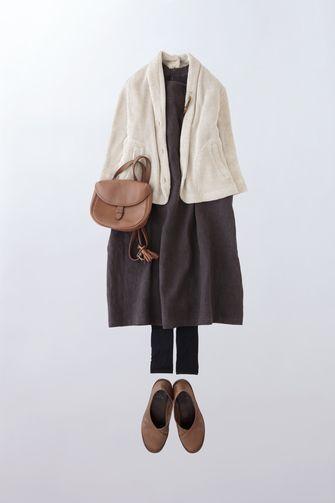 写真:ダークブラウンのワンピースに白のやわらかなジャケットを羽織って。