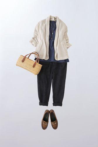 写真:トップスはネイビーのインナーに白のやわらかなジャケットを羽織って。ボトムスは黒のテーパードパンツ。