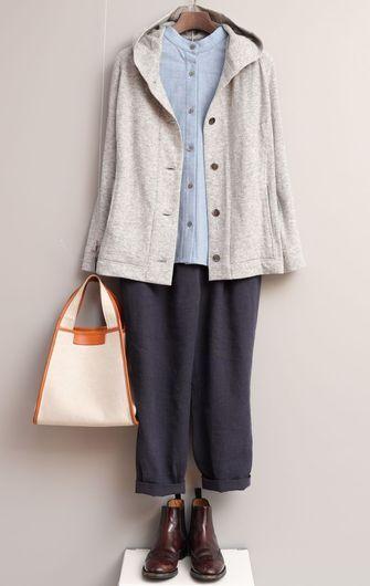 写真:サックスブルーのスタンドカラーシャツにネイビーのテーパードパンツ。フード付きのカジュアルなジャケットを羽織って。