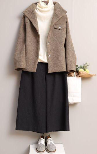 写真:白いタートルネックに黒いキュロットパンツ。ベージュのショートコートを羽織って。