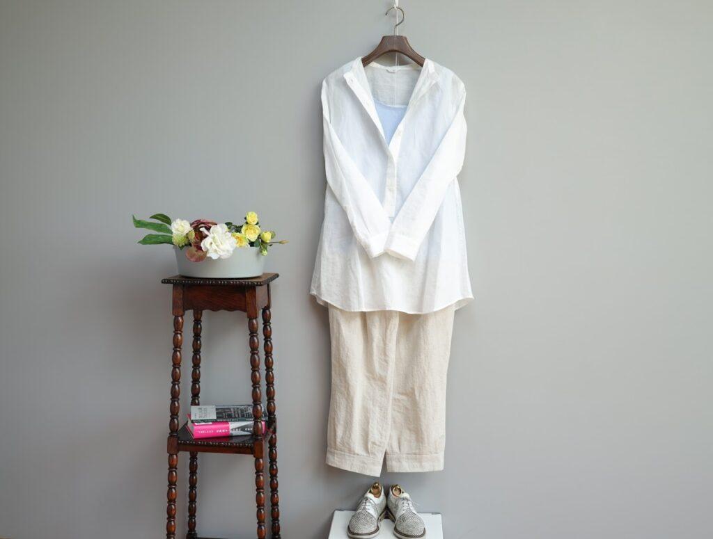 コーディネート写真:トップスはライトブルーの海島綿のタンクトップに白いコットンラミーのスタンドカラーシャツのボタンを開けて。ボトムスは生成りオーガニックコットンリネンのデザインテーパードパンツを合わせた同系色コーディネート。