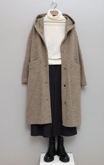 写真:白いクルーネックのカットソーに黒のキュロットパンツ。フード付きのベージュのロングコートを羽織って。