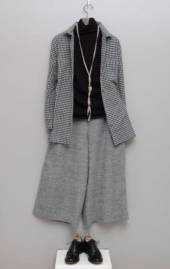 写真:黒のタートルネックにグレーのキュロットパンツ。ギンガムチェックのジャケットを羽織って。