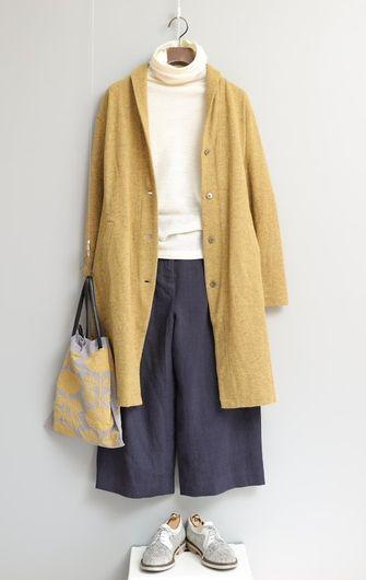 写真:白いタートルネックのカットソーにダークグレーのキュロットパンツ。黄色のコートを羽織って。