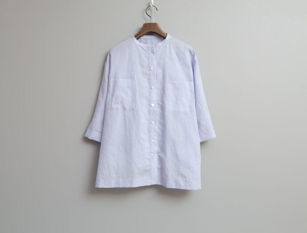写真:細めのスタンドカラーの前開きシャツ。両胸にポケットつき。