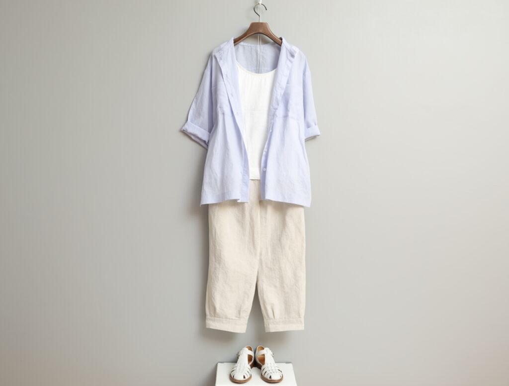 写真:白のタンクトップにサックスブルーのシャツを羽織って。ボトムスは生成りのテーパードパンツ。