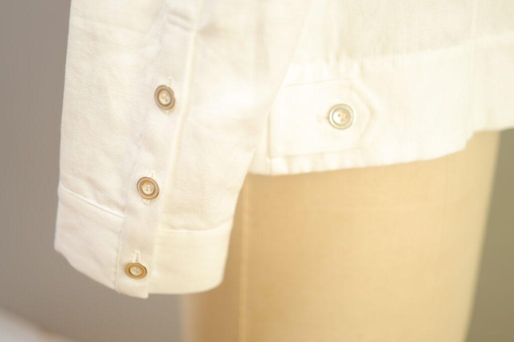 写真:袖口に3つのボタン。脇にボタン付きの小さなベルト。