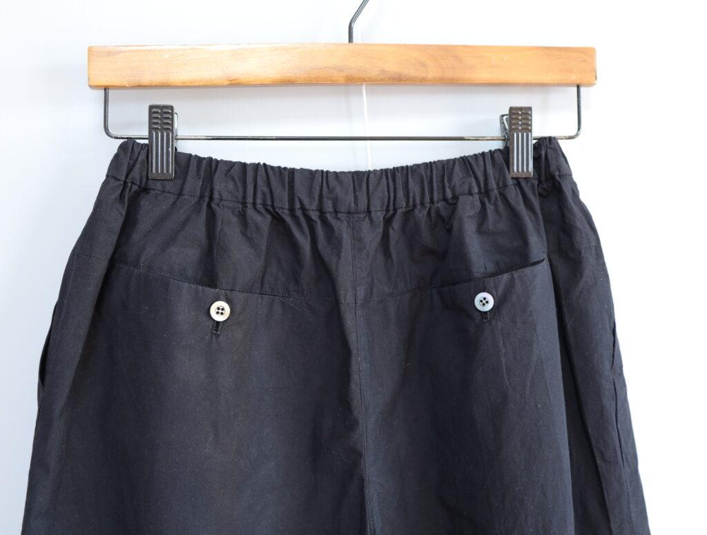 写真:バックに2つのポケット。白いボタンがアクセント。