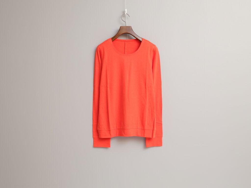 写真:鮮やかなオレンジのUネックプルオーバー。