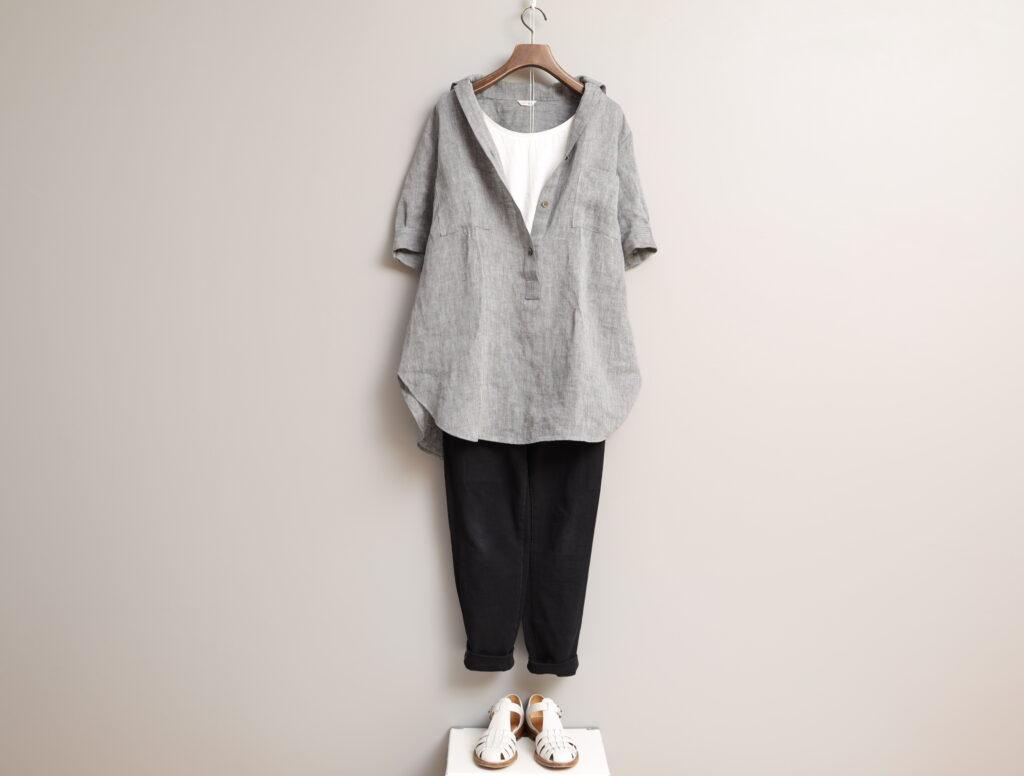 コーディネート写真:黒のテーパードパンツと合わせ、シャツのボタンを開けて白のインナーをのぞかせて。